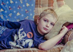 cranky boy lying down to keep calm